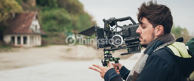 Behind the scene. Cameraman shooting film scene with his camera : Stock Photo