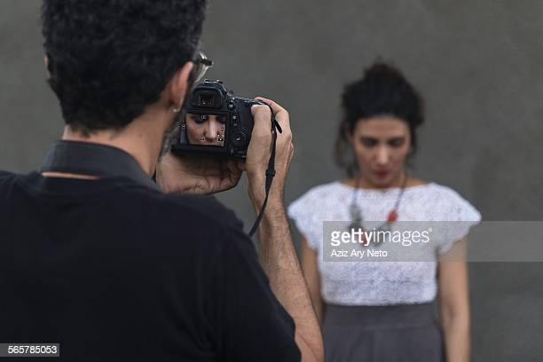 Behind the scenes of an urban fashion shoot with female model and male photographer