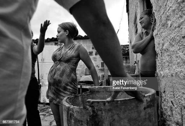 Behind their home Carla de Sousa who is pregnant left and her mother Maria de Sousa listen as mosquito control agents give tips on how to prevent...