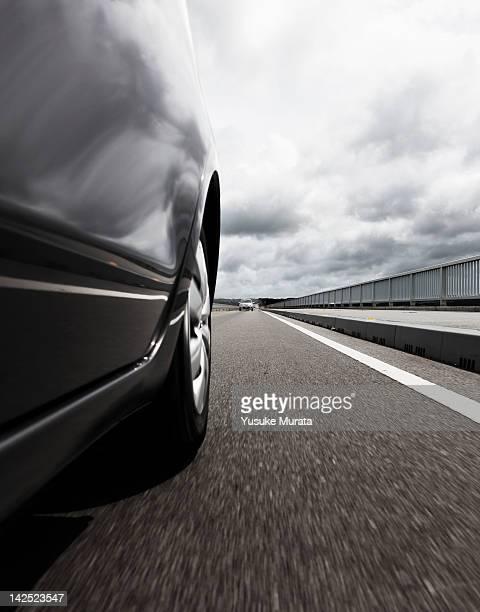 Behind view of car driving along coastal road