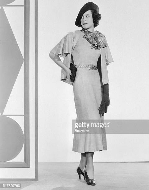 Beige Alpaca is used on one of Kitty Carlisle's smart fall outfits here The shortsleeved frock has a scarf and belt of taffeta with an angora thread...