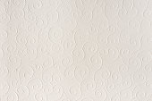 Old white, beige paper sheet texture background. Shells, waves, circles, shapes embossed pattern. Strong light, shadows.