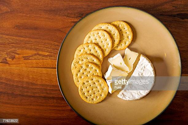 Beige plate of soft cheese and crackers on wooden table