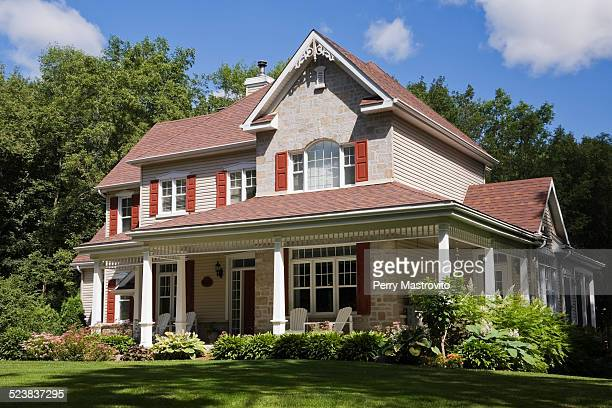 Beige stone with white and red trim residential cottage style house, Quebec, Canada
