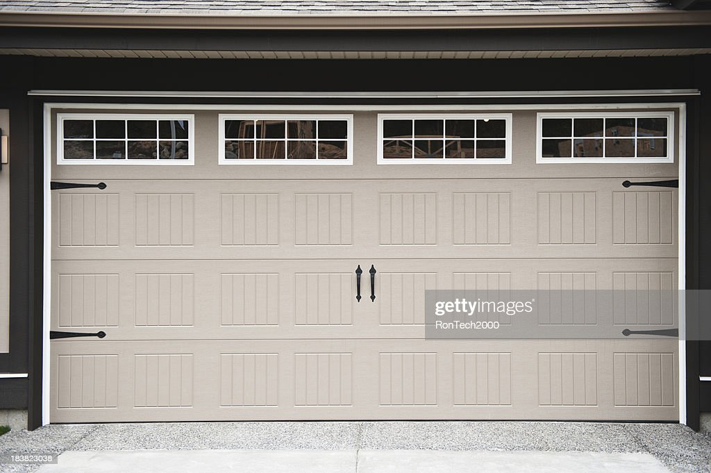 A Beige Two Car Garage Door With Paneled Windows Along Top : Stock Photo