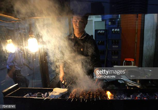 A barbecue meat vendor roasts skewers of mutton at a restaurant in Beijing 04 November 2006 China has seen a massive increase in greenhouse gas...