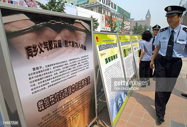 A Chinese policeman walks past anti corruption billboards on display in Central Beijing 11 June 2007 Unable to stem a rising tide of corruption China...
