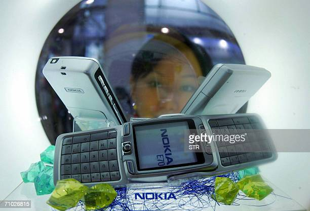 A Chinese promoter shows off Finland's Nokia new mobile phones at a hitech fair in Beijing 23 May 2006 The number of mobile phone subscribers in...