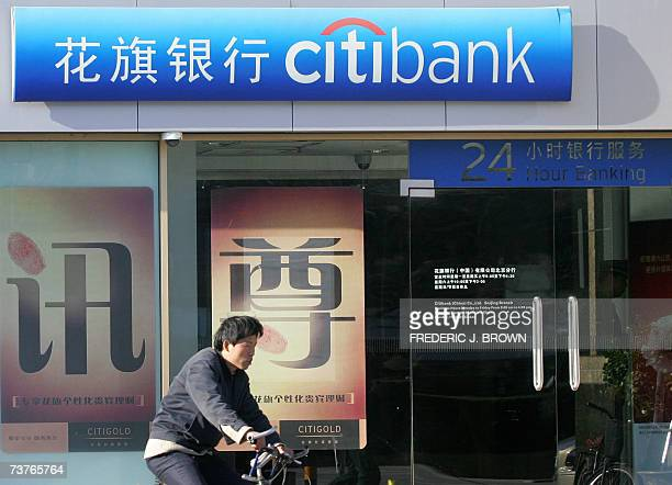 A cyclist rides past a branch of USbased Citibank in Beijing 02 April 2007 The USbased Citigroup and Britain's HSBC were among a group of banks that...
