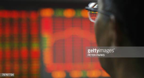 An investor looks at an electronic board at a securities brokerage in Beijing 27 july 2007 Insider trading and other illegal share activities are...