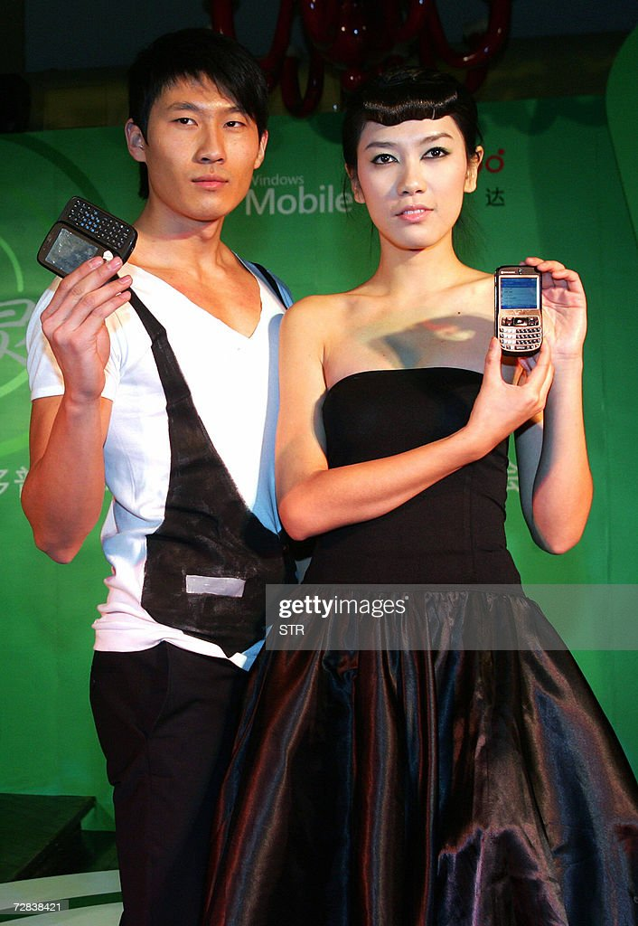 Chinese promoters show off the latest handsets in Beijing 16 December 2006 China's own technology for 'third generation' cellphones is ready for...