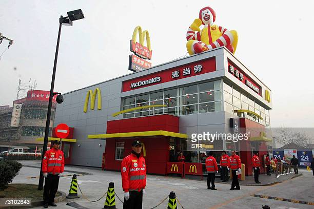Chinese staff wait for the first customers at the opening of a McDonald's drivethru outlet built next to a gas station in Beijing 19 January 2007 US...
