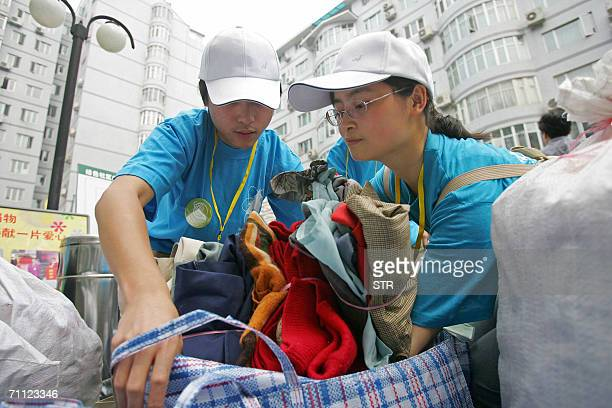 Chinese volunteers collect the old clothes donated by residents at a flea market as part of the World Environment Day program in Beijing 04 June 2006...