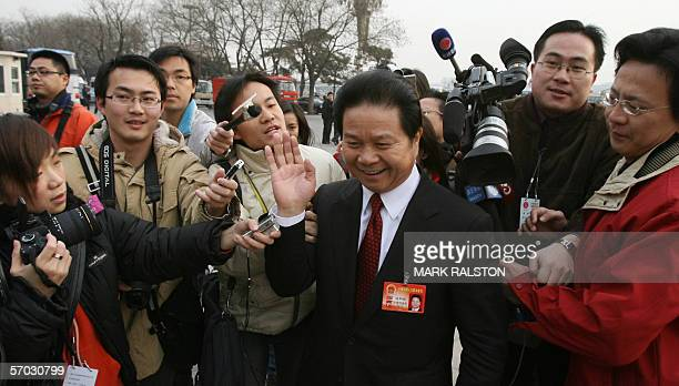 Deputy Governor of Guangdong Province Tang Bingquan tries to evade reporters before a session of the National People's Congress at the Great Hall of...