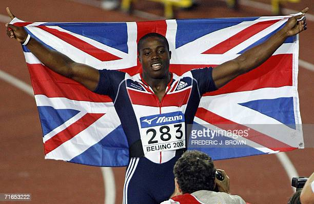 Harry AikinesAryeetey of Great Britain celebrates with the national flag after winning the men's 100m final 16 August 2006 in Beijing at the 11th...