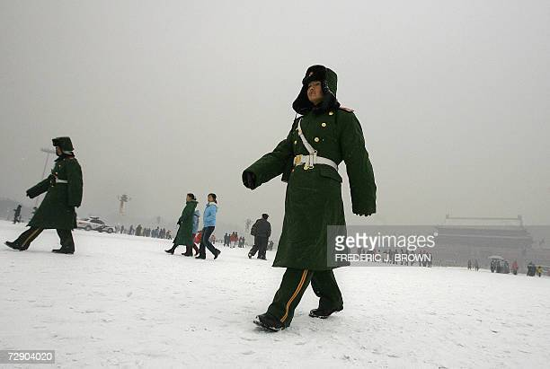 Paramilitary police patrol Tiananmen Square under a light snowfall during the first snow of the winter in Beijing 30 December 2006 China experienced...