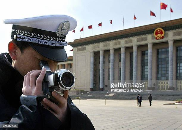 This 03 March 2004 photo shows a policeman videotaping in front of the Great Hall of the People in Beijing ahead of the opening session of the...