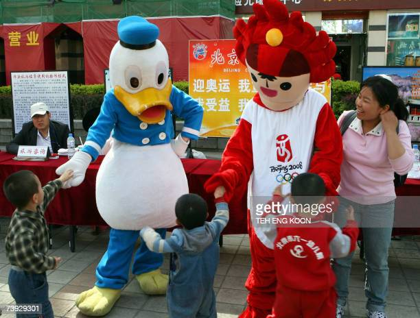 Two Chinese travel agency workers wearing Walt Disney character Donald Duck and Beijing 2008 Olympic games mascot costumes promote China's tourism in...