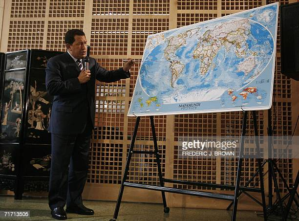 Visiting Venezuelan president Hugo Chavez points to Venezuela on a world map 25 August 2006 during a press conference at the Venezuelan embassy in...