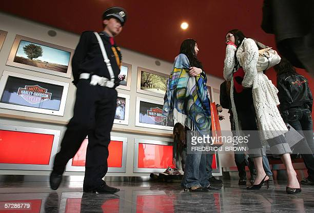Women chat as a security guard walks past inside the sales showroom during the opening of Beijing HarleyDavidson's first authorized dealership in...