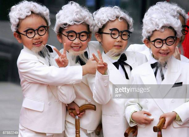 Young Chinese children dress up as US fastfood chain Kentucky Fried Chicken's Colonel Sanders lookalikes during a store opening ceremony in Beijing...