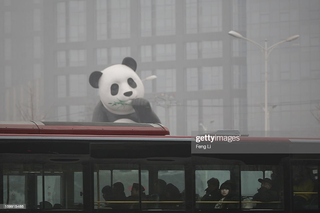 Beijing residents take bus through a panda sculpture during severe pollution on January 23, 2013 in Beijing, China. The air quality in Beijing on Wednesday hit serious levels again, as smog blanketed the city.