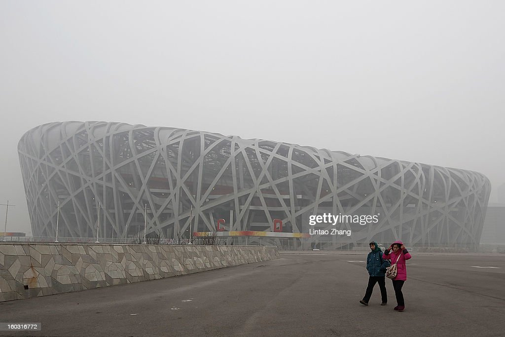 Beijing residents wearing masks walk in front of a fog-shrouded National Stadium as severe pollution continues to affect the capital on January 29, 2013 in Beijing, China. China's ruling Communist party has announced temporary emergency measures in an attempt to combat the current hazardous levels of pollution enveloping Beijing.