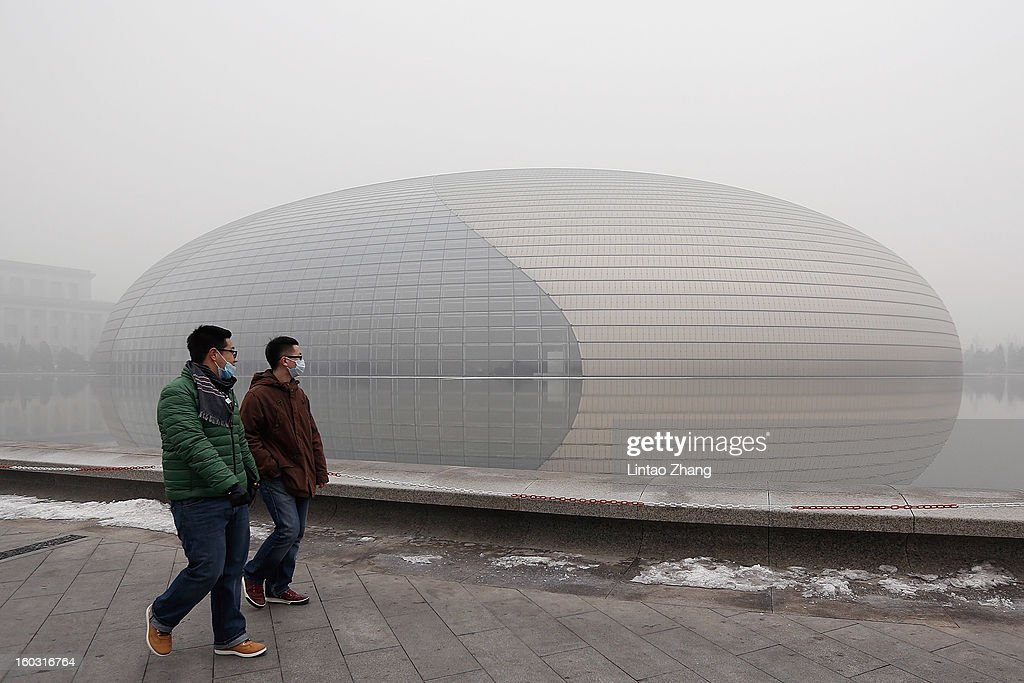 Beijing residents wearing masks walk in front of a fogshrouded National Grand Theater as severe pollution continues to affect the capital on January...