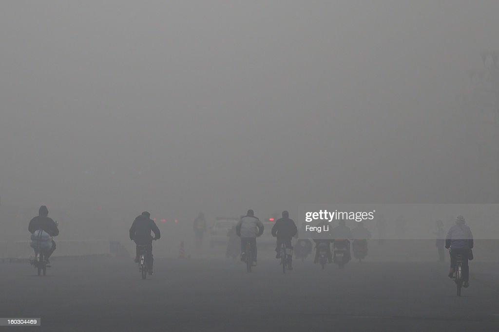 Beijing residents wearing the mask ride amid fog during severe pollution on January 29, 2013 in Beijing, China. The 4th dense fog envelops Beijing with pollution at hazardous levels in January.