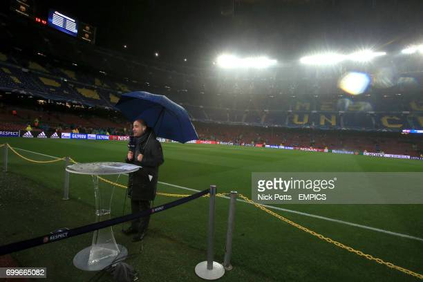 A beIN sports presenter shelters under an umbrella before the game as heavy rain falls over the Nou Camp