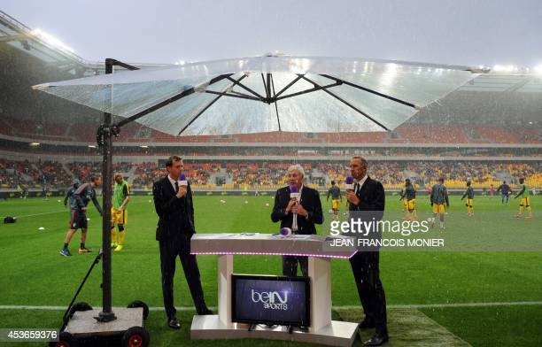 BeIn Sports TV channel's journalists Florian Genton Luis Fernadez and Eric Roy speak under a giant umbrella prior to the French L1 football match...