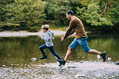 Little boy is being chased in to the lake by his father while they are out hiking.