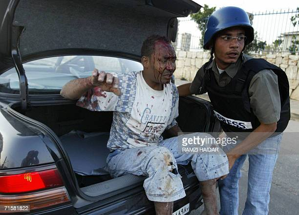A journalist helps a Sudanese man wounded in Israeli air strikes early 04 August 2006 in the southern suburbs of Beirut a stronghold of Hezbollah...