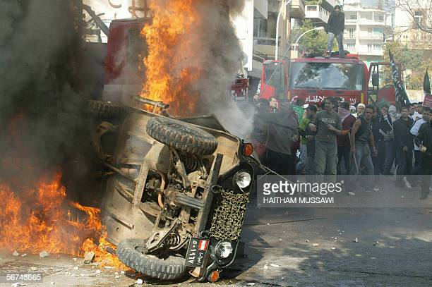 A Lebanese army jeep is set on fire by protesters during a violent demonstration 05 February 2006 in Beirut against the publication of cartoons...