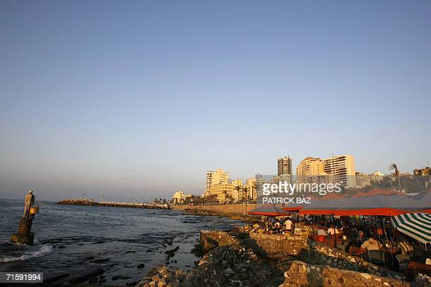 A Lebanese man fishes while others dine at a seaside cafe in Beirut's corniche at sunset 05 August 2006 A Hezbollah government minister said today...