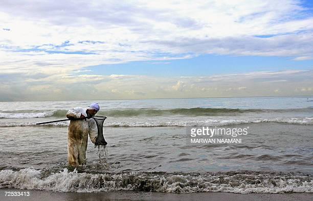 A Lebanese volunteer from the 'Bahr Lubnan' NGO cleans the water at a beach in Beirut 14 November 2006 Almost three months after the Isareli...