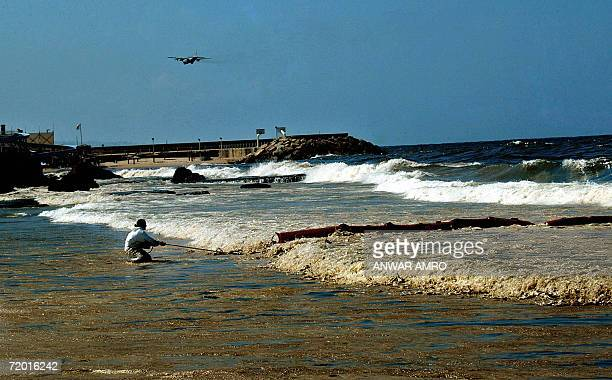 A Lebanese volunteer of the Green Line pulls fixes floating booms at the waters of a Beirut beach to prevent an oil spill from reaching the shore 02...