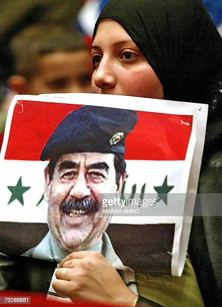 A Lebanese woman holds a poster of late Iraqi leader Saddam Hussein during a ceremony in Beirut to mark the 40th day since his execution 11 February...