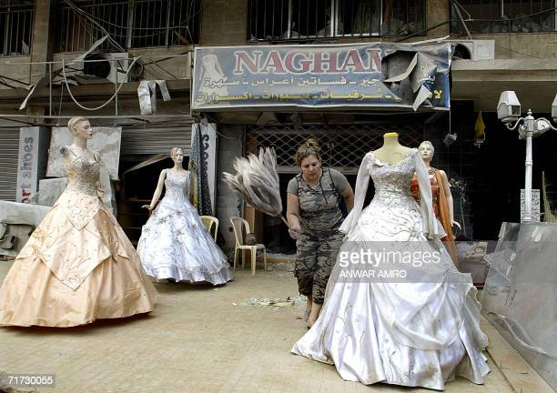 A Lebanese woman removes dust from a wedding dress outside her partially destroyed shop in Beirut's southern suburb 28 August 2006 UN Secretary...