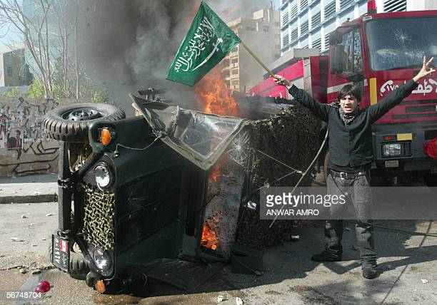 A protester waves a Saudi flag as he flashes the Vsign of victory next to a Lebanese army jeep set on fire by protesters during a violent...