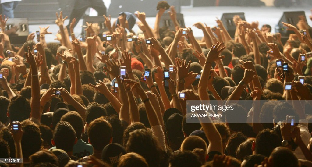 Lebanese fans use their mobile phones to take pictures of US rapper 50 Cent during his concert at Biel hall in downtown Beirut late 10 June 2006. AFP PHOTO/NWAR AMRO