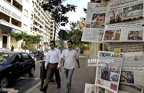 Lebanese men walk past a kiosk displaying newspapers with images of assassinated Lebanese Industry Minister Pierre Gemayel in Beirut 22 November 2006...