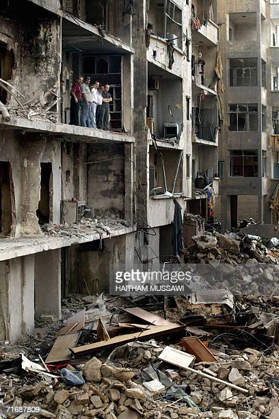 Lebanese nationals standing on a balcong of a destroyed building look at the visit of Emir of Qatar Sheikh Hamad bin Khalifa alThani to the...