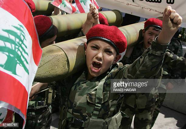 Lebanese Shiite Muslim children carrying on their shoulders mock katyusha missiles shout antiIsraeli slogans during a Hezbollah rally outside the...