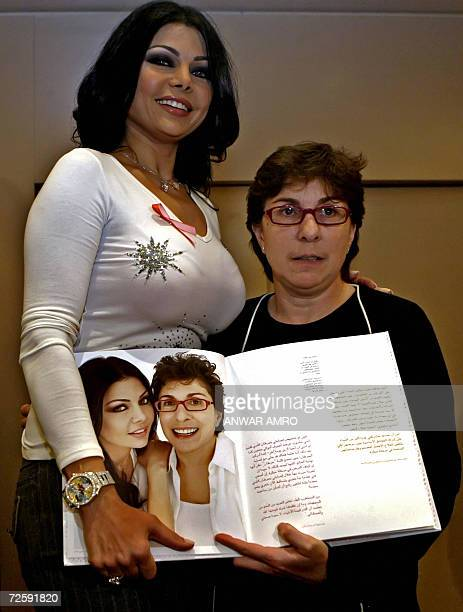 Lebanese singer Haifa Wehbe poses for a picture with breast cancer patient Lina Haddad during a press conference to promote a book about Breast...