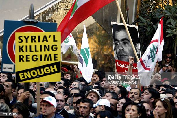 Mourners gather near a sign denouncing Syria outside the Maronite St George Cathedral in the heart of Beirut during the funeral of assassinated...