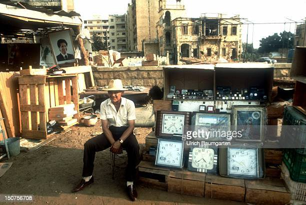 LEBANON Beirut Stalls selling birds fruit vegetables flowers and clocks in front of ruins in Beirut