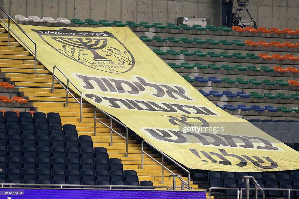 OUT== Beitar Jerusalem fans display a banner which reads in Hebrew ''Violence and racism not in our stadium'' during a match againts Bnei Sakhnin at the Teddy Kollek Stadium in Jerusalem on February 10, 2013 during the teams State match qualification football game. The Beitar Jerusalem soccer club hosted the Israeli Arab team Bnei Sakhnin in a highly charged atmosphere, only three days after indictments were filed against four Beitar fans over charges relating to racism. AFP PHOTO / STR