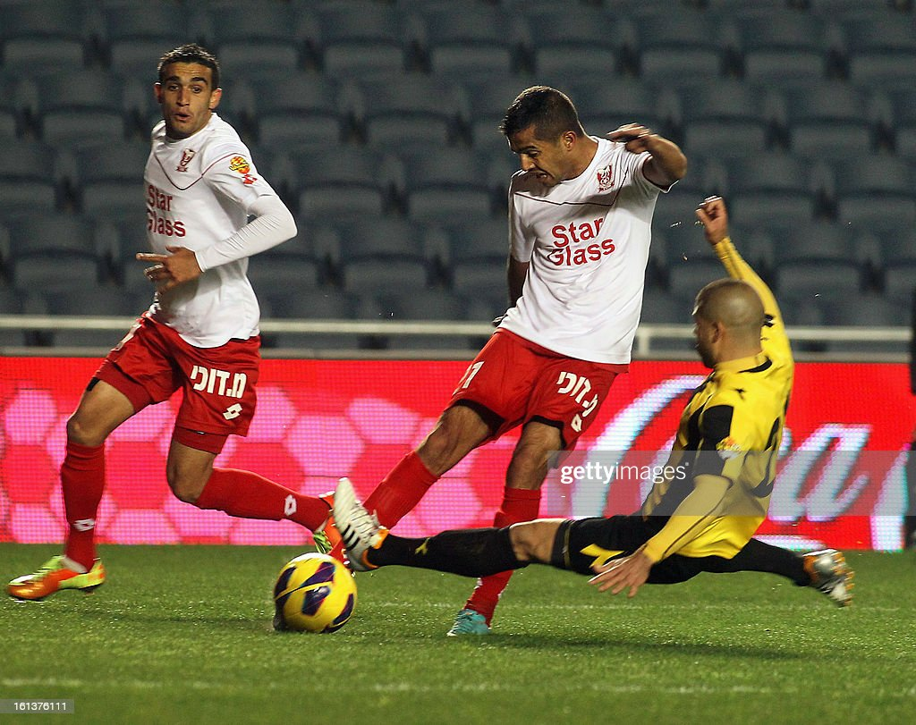 OUT== Beitar Jerusalem player Kobi Moyal (R) fights for the ball with Bnei Sakhnin player Ahmed Kasoum (L) at the Teddy Kollek Stadium in Jerusalem on February 10, 2013 during the teams State match qualification football game. The Beitar Jerusalem soccer club hosted the Israeli Arab team Bnei Sakhnin in a highly charged atmosphere, only three days after indictments were filed against four Beitar fans over charges relating to racism. AFP PHOTO / STR