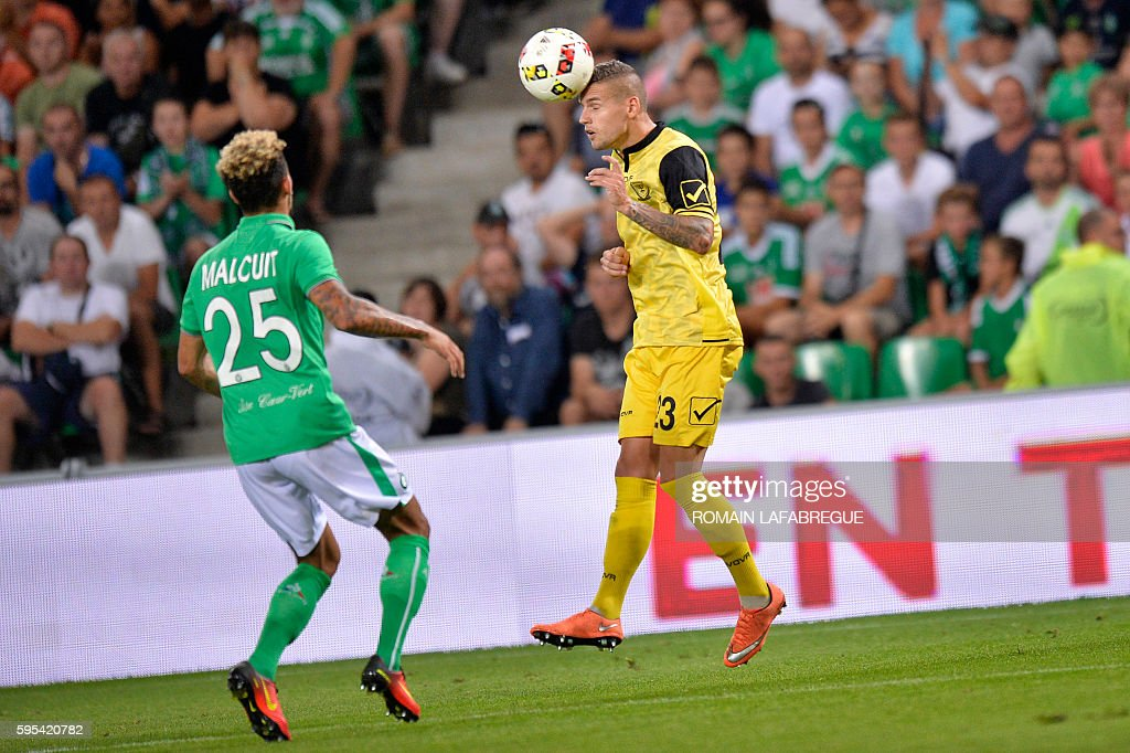Beitar Jerusalem's German defender Marcel Heister heads the ball in front of SaintEtienne's French defender Kevin Malcuit during the UEFA Europa...
